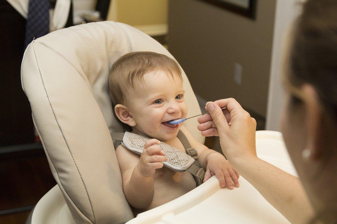 bébé souriant à qui une femme donne à manger à la petite cuillère