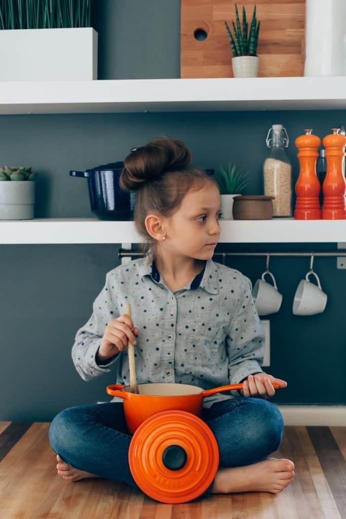 petite fille assise sur une table en bois qui tient une casserole orange sur ses genoux et qui brasse avec une cuillère en bois