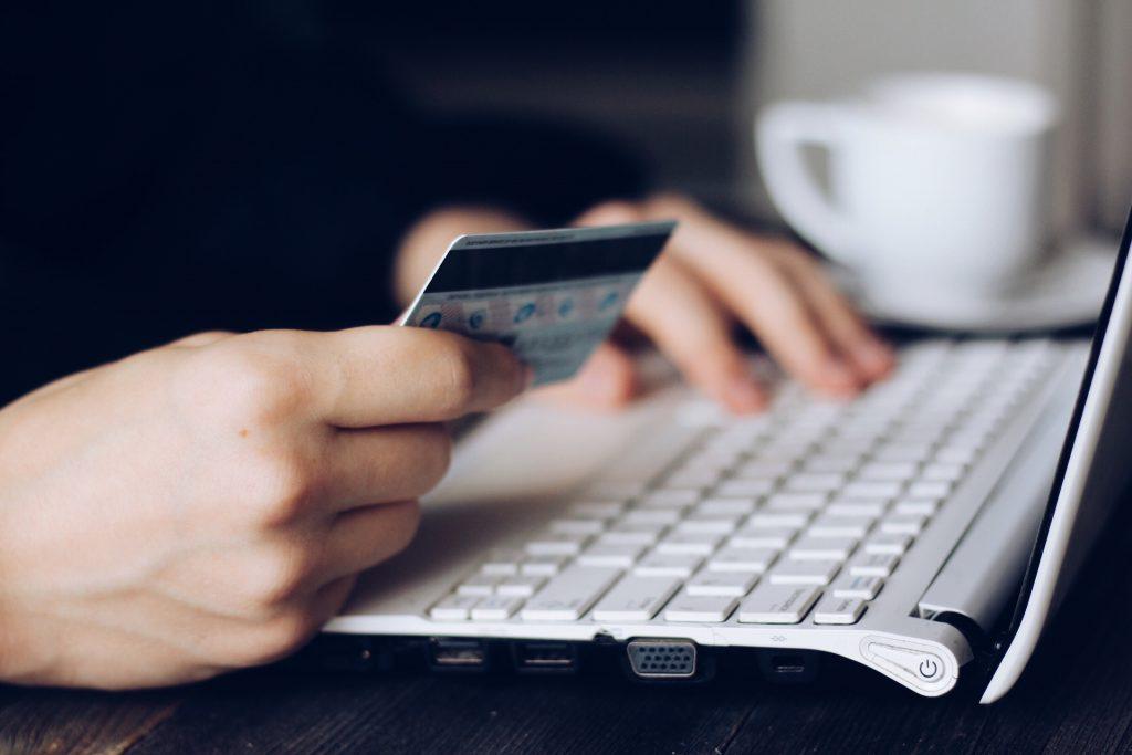 zoom sur les mains d'une personne qui tient une carte bancaire dans une main et tape sur un clavier d'ordinateur de l'autre