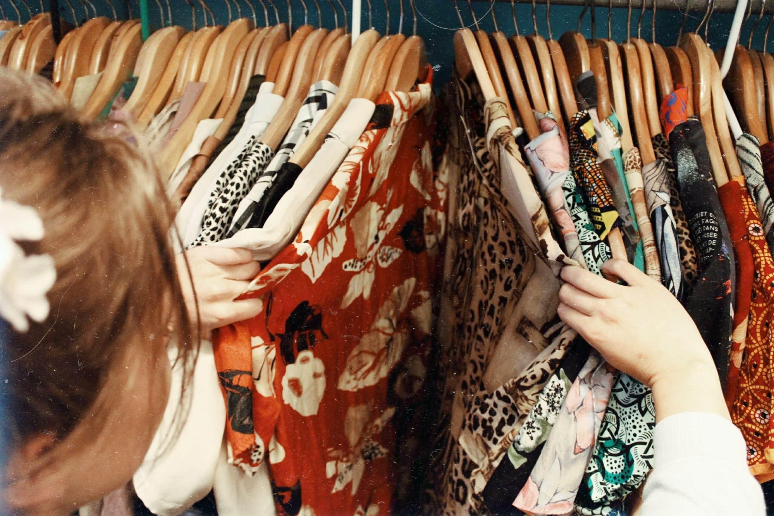 femme qui regarde des vêtements sur des cintres