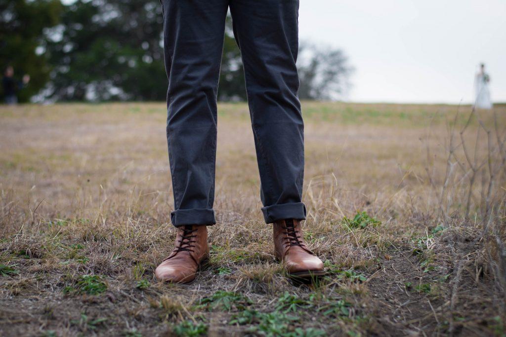 jambes d'un homme portant un chino foncé et des bottines à lacets marron