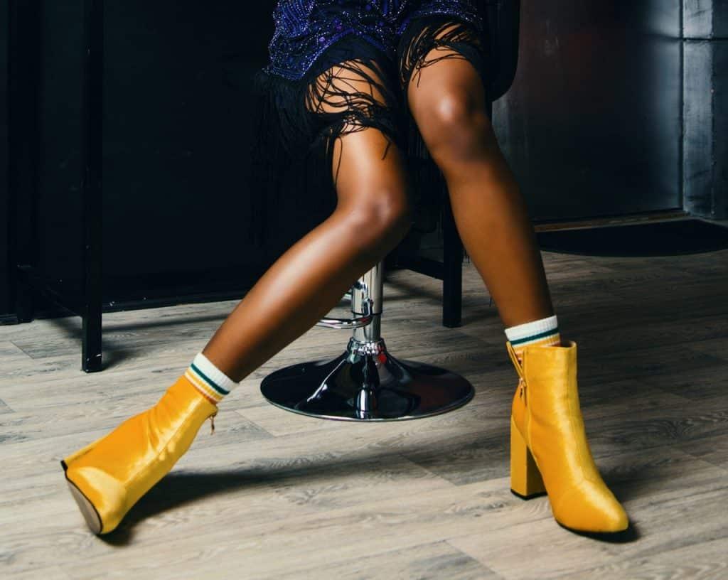 jambes d'une femme portant des bottines jaunes