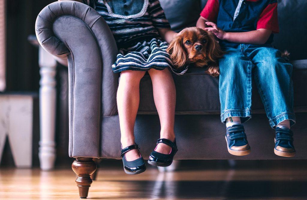 deux enfants assis sur un canapé avec un chien couché entre eux