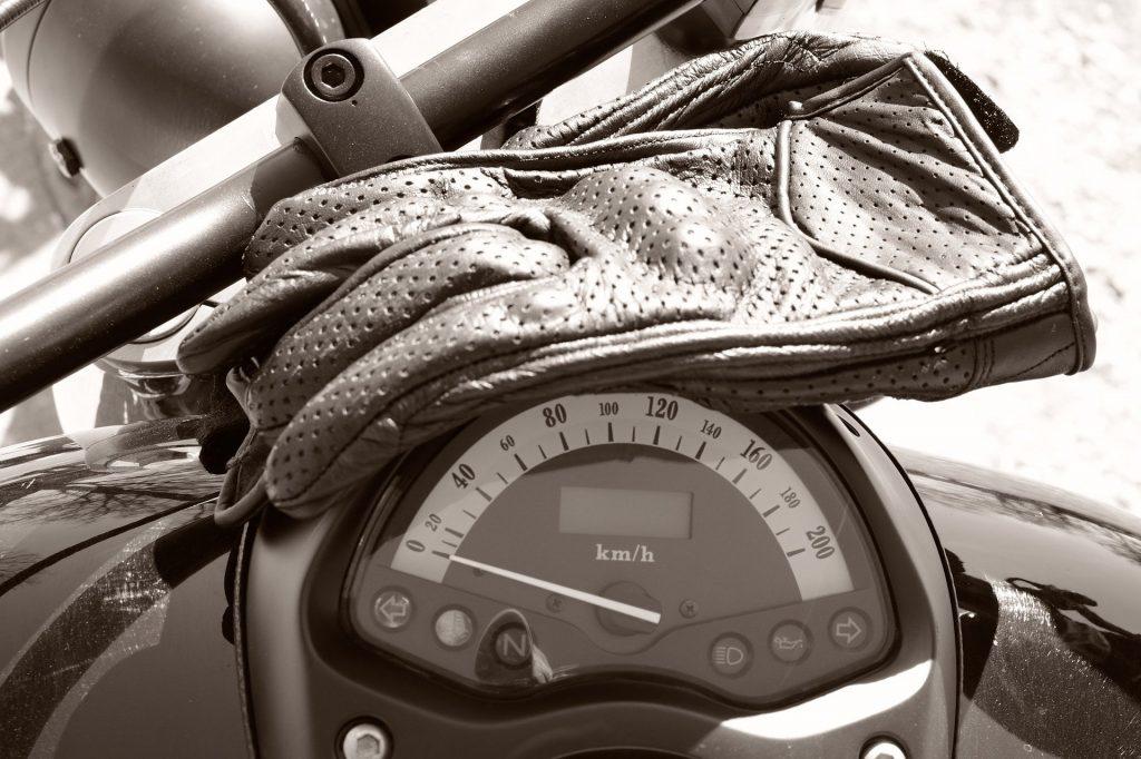 Gants posés sur le compteur de vitesse d'une moto