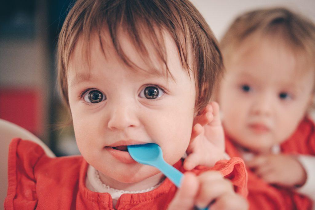Enfants jumeaux qui prennent leur repas ensemble