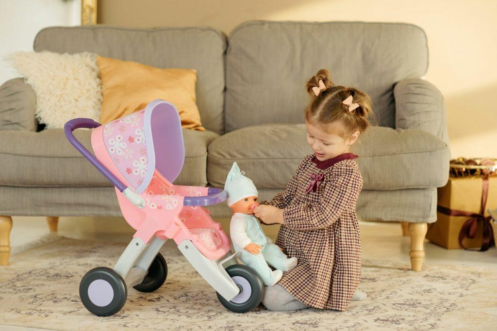 petite fille qui joue avec sa poupée et une poussette pour poupon dans le salon