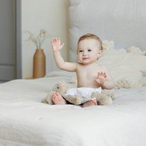 nouveau né assis sur un lit avec son doudou de naissance sur les genoux